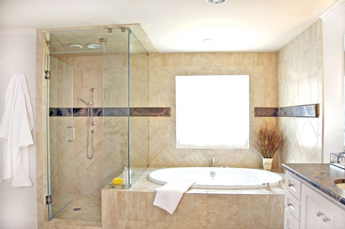 frameless glass shower and tub with marble slab accent band in Dallas master bathroom remodel