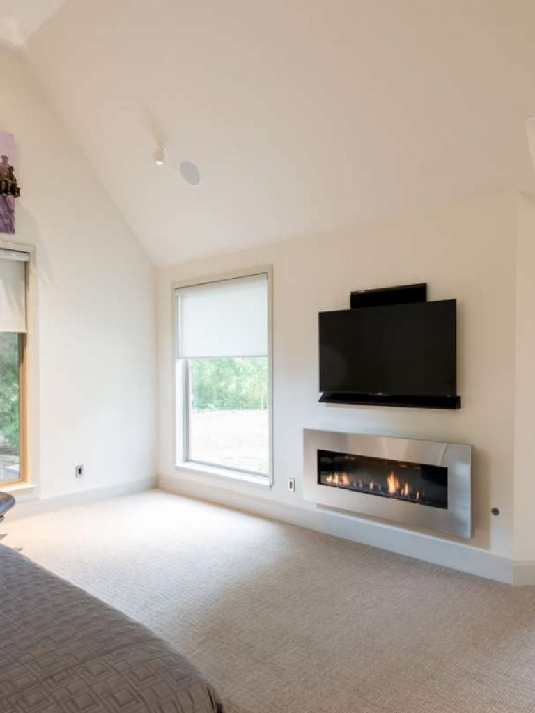 stainless steel fireplace in master bedroom of dallas whole home remodel