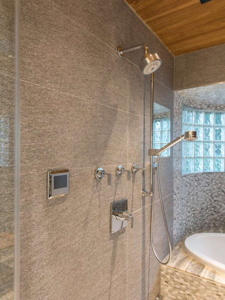 steam, multiple shower heads and a heated shaving mirror in master bathroom of dallas whole home renovation