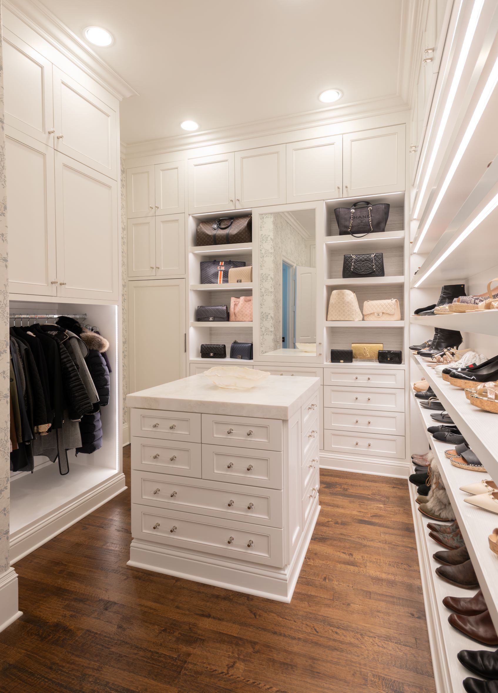 A master closet with custom cabinets, shoe storage, and an island.