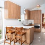 Vertical grain wood cabinets with white quartz countertops of kitchen remodel in dallas